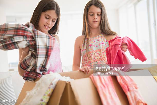 Caucasian twin sisters donating clothing