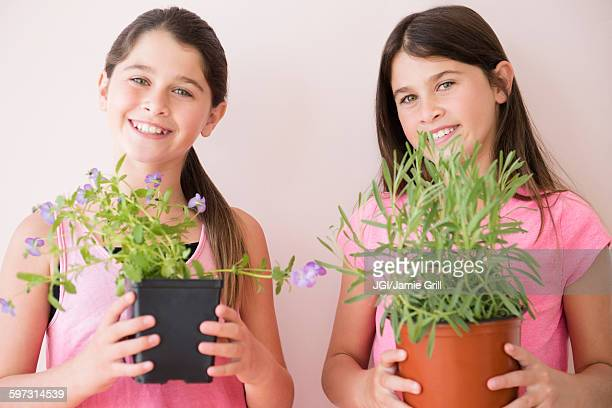 Caucasian twin sisters holding potted plants