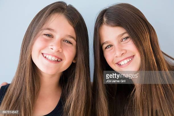 Caucasian twin sisters smiling