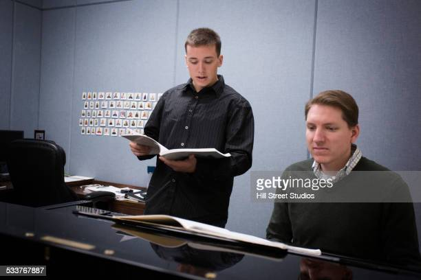 caucasian vocal teacher and student singing at piano - pianist front stock pictures, royalty-free photos & images