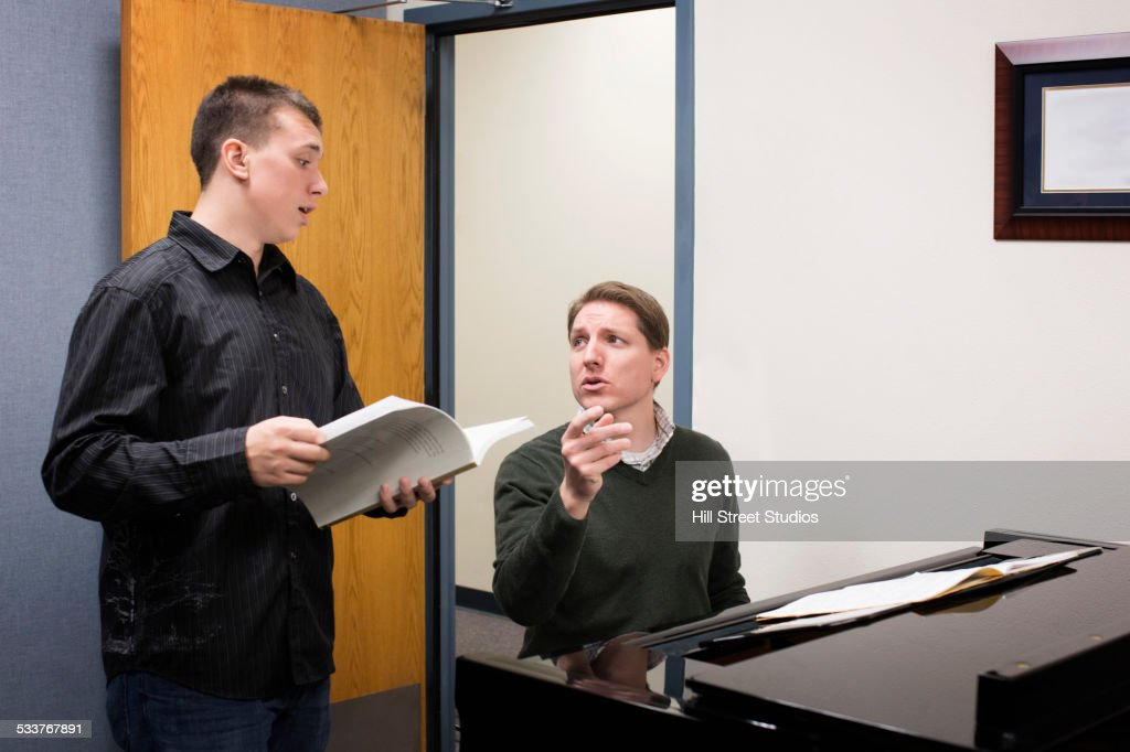 Caucasian vocal teacher and student singing at piano : Foto stock