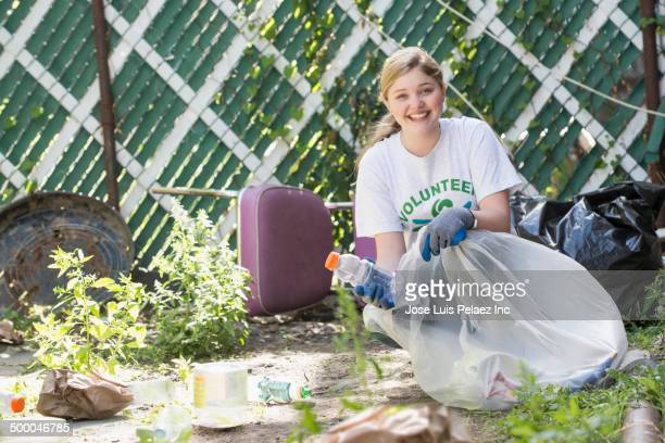 caucasian volunteer picking up litter in urban garden - city cleaning stock pictures, royalty-free photos & images