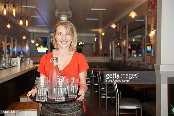 Caucasian waitress carrying tray of water glasses in bar
