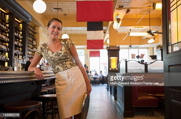 Caucasian waitress leaning on bar in restaurant