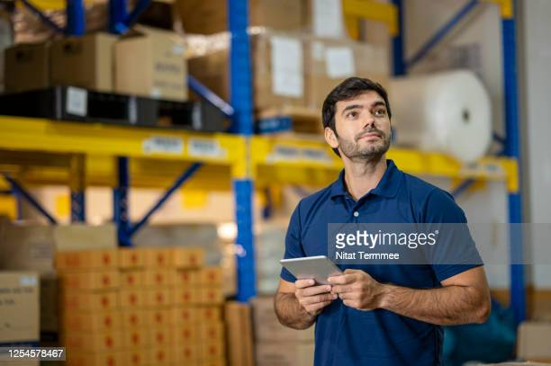 caucasian warehouse worker with digital tablet. worker in polo shirt uniform working with checklist taking stock in a distribution warehouse. - polo shirt stock pictures, royalty-free photos & images