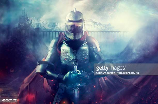 caucasian warrior wearing armor and cape on foggy battlefield - ritter stock-fotos und bilder