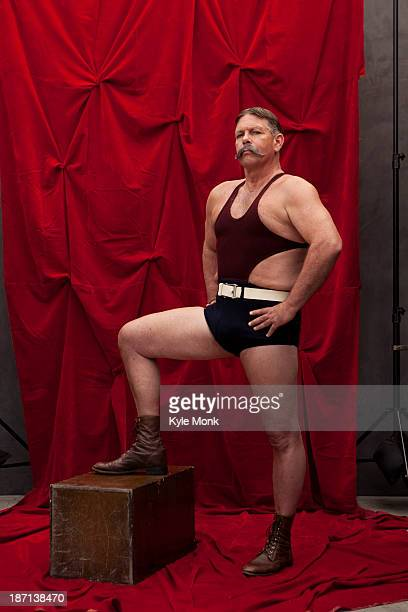 Caucasian weight lifter posing by curtain