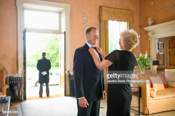 Caucasian woman adjusting tie for husband in formal parlor
