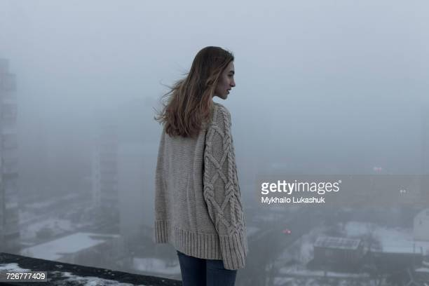 Caucasian woman admiring cityscape on rooftop in winter