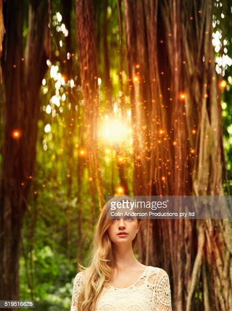 Caucasian woman admiring glowing lights in forest
