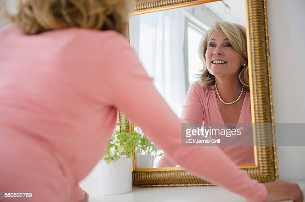 Caucasian woman admiring herself in mirror