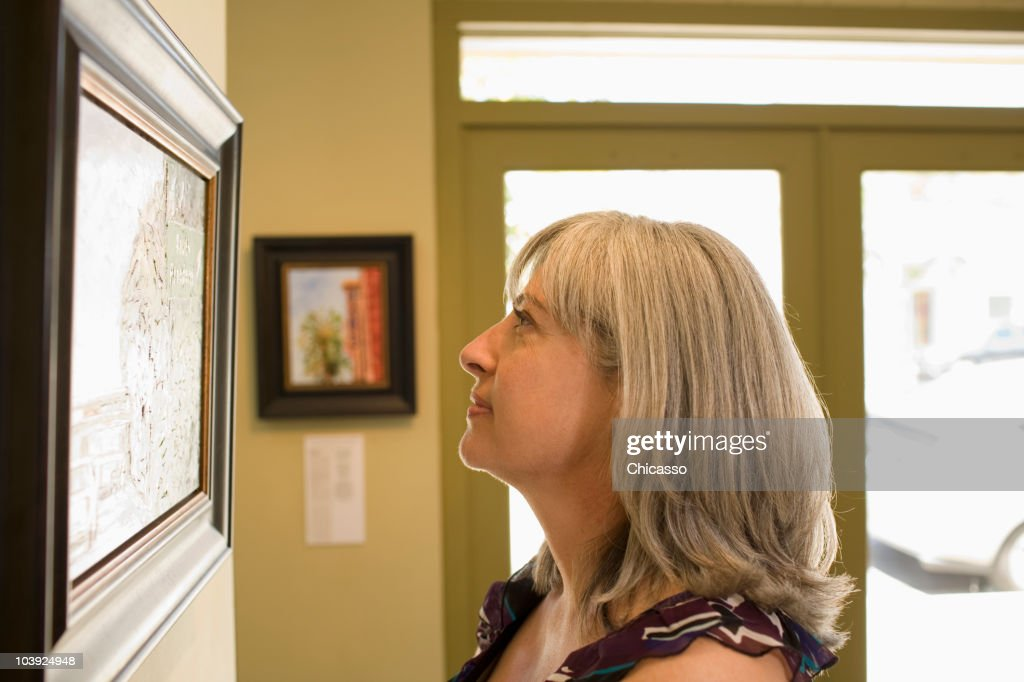 Caucasian woman admiring painting in gallery : Stock Photo