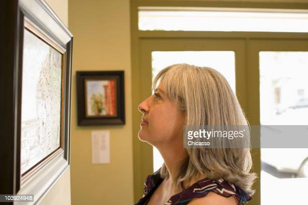 caucasian woman admiring painting in gallery - painting art product stock pictures, royalty-free photos & images