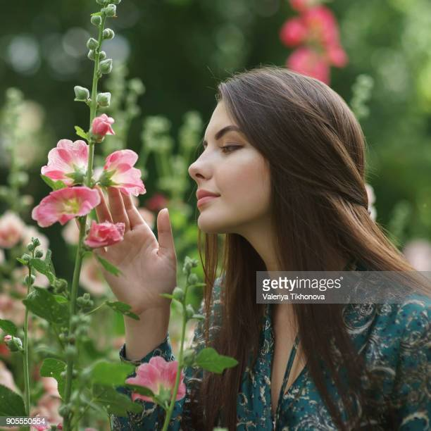 Caucasian woman admiring pink flowers