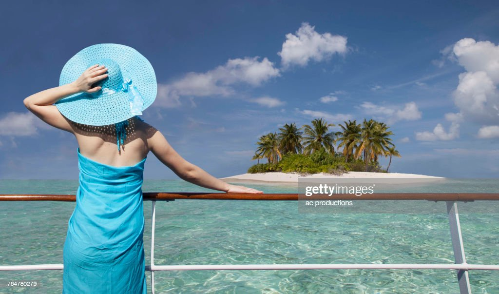 Caucasian woman admiring scenic view of island from boat : Stock Photo