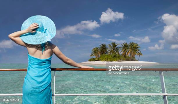 Caucasian woman admiring scenic view of island from boat