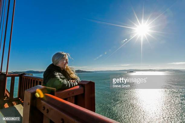 Caucasian woman admiring scenic view on bridge