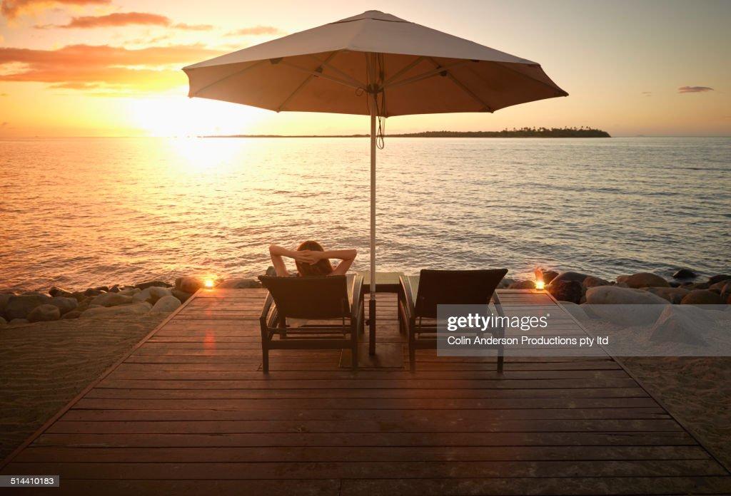 Caucasian woman admiring sunset over water, Denarau Island West, Nadi, Fiji : Stock Photo