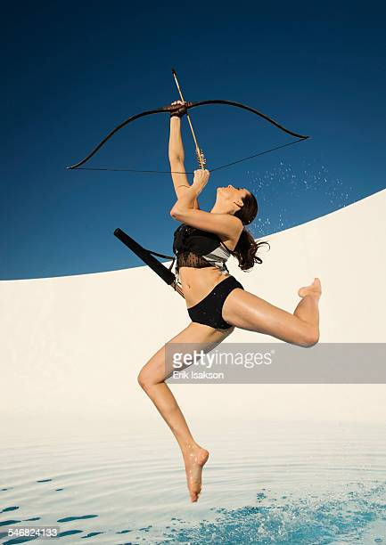 Caucasian woman aiming bow and arrow