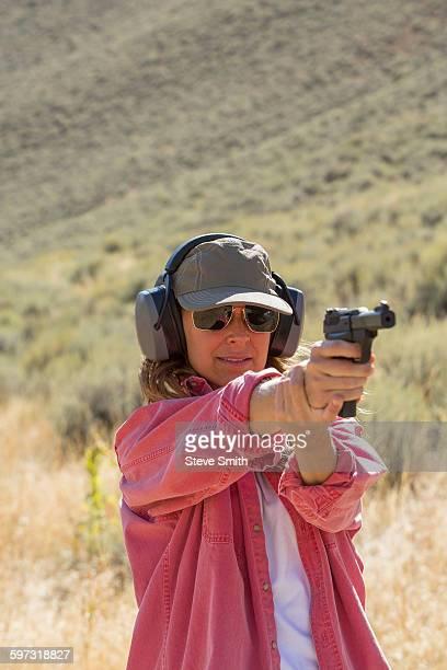 Caucasian woman aiming gun outdoors