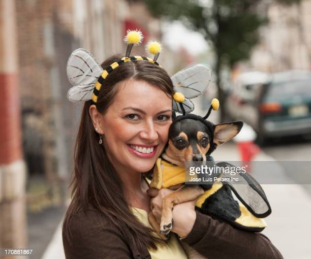 Caucasian woman and dog in bee costumes