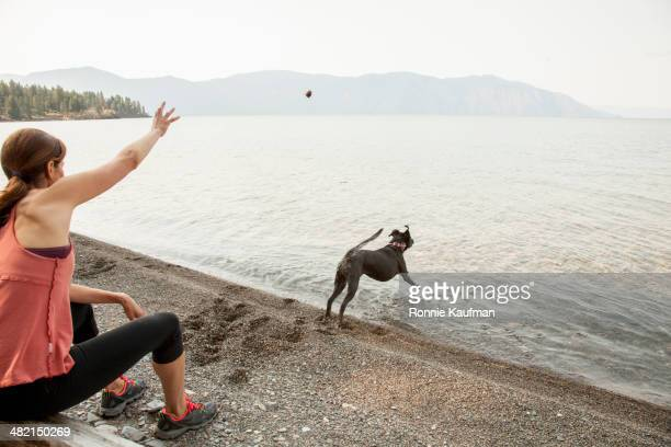 Caucasian woman and dog playing fetch by lake
