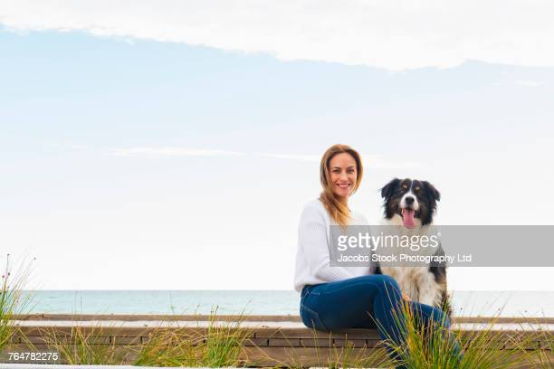 caucasian woman and dog sitting on boardwalk - border collie fotografías e imágenes de stock