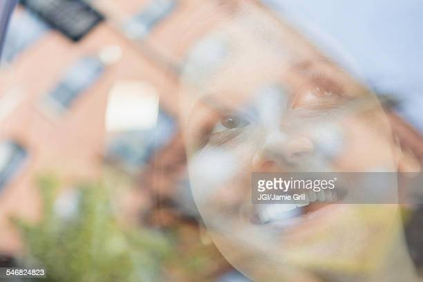 Caucasian woman and reflection of apartment buildings in window