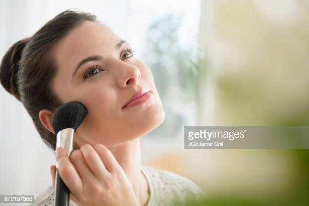 Caucasian woman applying blush