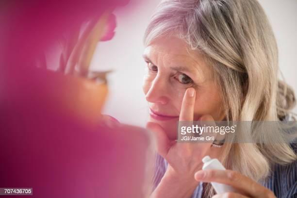 Caucasian woman applying cream to wrinkle near eye