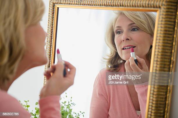 Caucasian woman applying lipstick in mirror