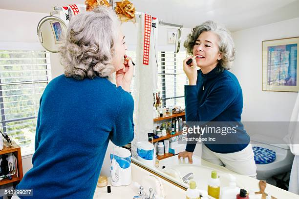 Caucasian woman applying makeup in mirror