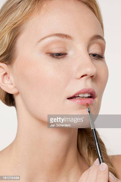 caucasian woman applying makeup - lip liner stock photos and pictures