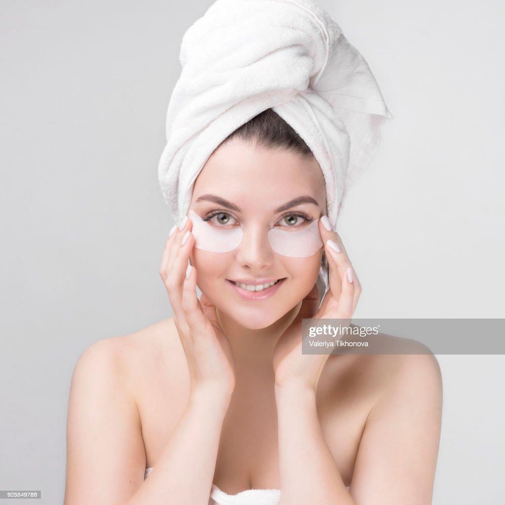 Caucasian woman applying makeup to cheeks : Stock Photo