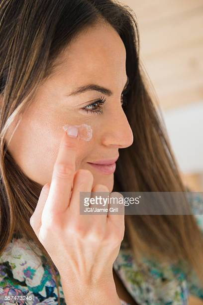 Caucasian woman applying moisturizer to face