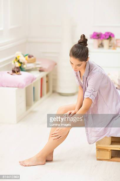 caucasian woman applying moisturizer to leg - frau gespreizte beine stock-fotos und bilder