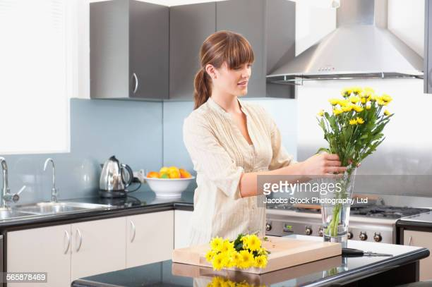 Caucasian woman arranging flowers in kitchen