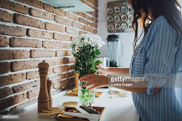 caucasian woman arranging flowers - vase stock pictures, royalty-free photos & images