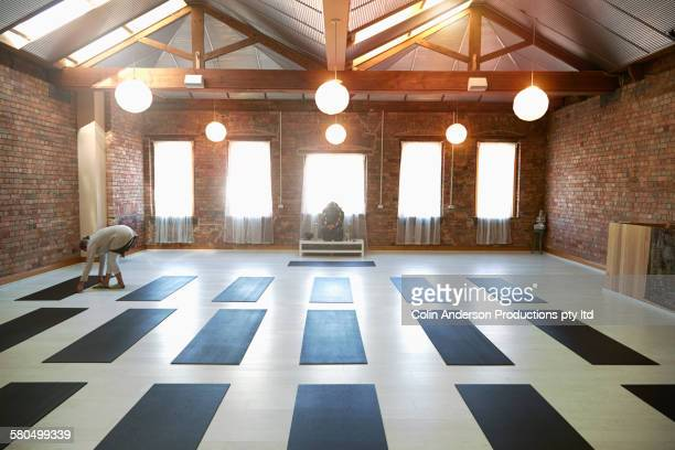 Caucasian woman arranging mats in yoga studio