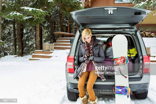 caucasian woman at car texting on cell phone in winter - loader reading stock pictures, royalty-free photos & images