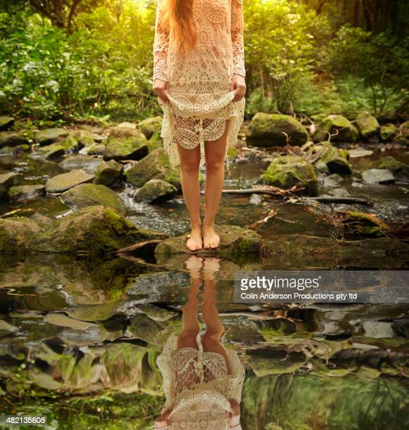 Caucasian woman at creek in woods