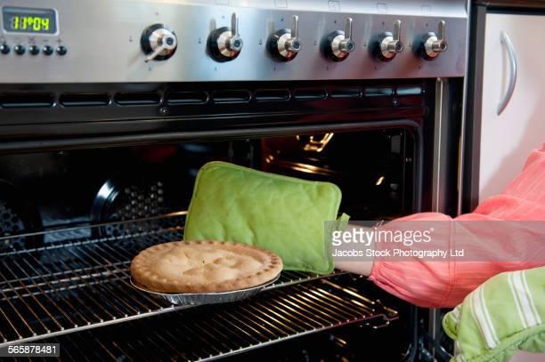 Caucasian woman baking pie in oven