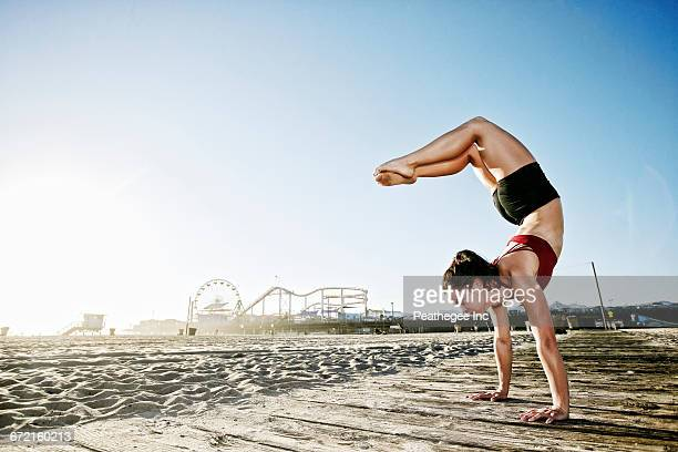 Caucasian woman balancing in handstand on beach boardwalk