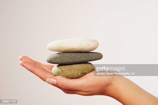 Caucasian woman balancing three rocks in palm