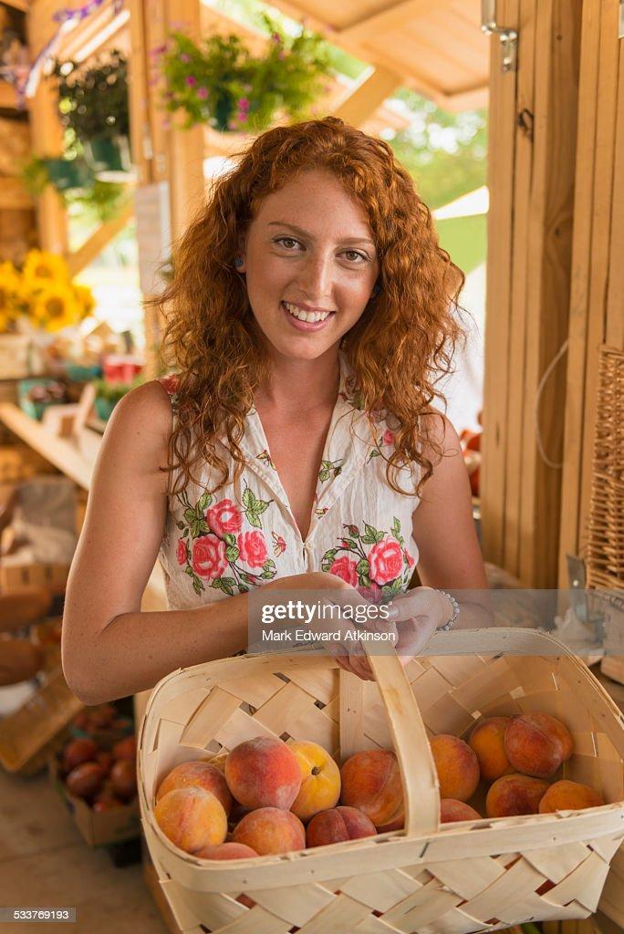 Caucasian woman basket of peaches at farmers market : Foto stock