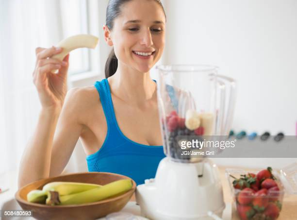 Caucasian woman blending fruit smoothie