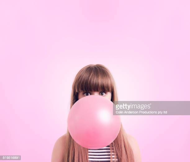caucasian woman blowing large bubble gum bubble - soplar fotografías e imágenes de stock