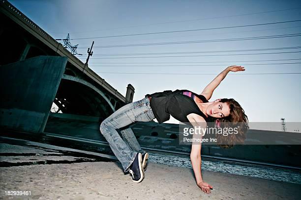 Caucasian woman break dancing under overpass