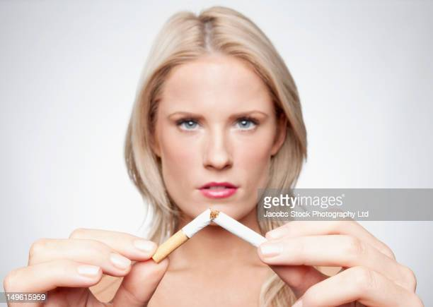 Caucasian woman breaking cigarette