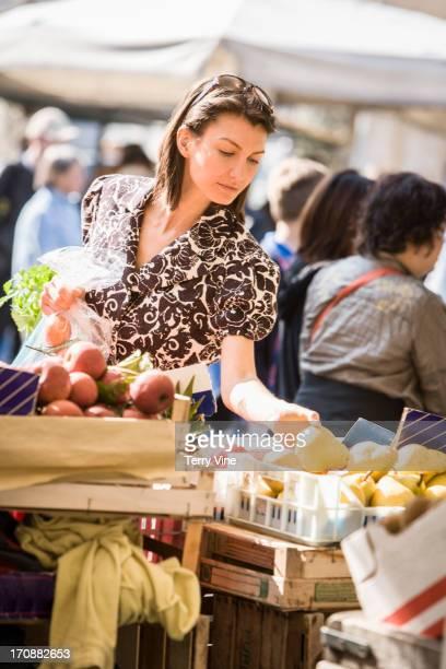 Caucasian woman buying produce at market